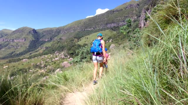Family hiking adventures A mother and her son enjoy hiking along a beautiful footpath in the mountains natal stock videos & royalty-free footage