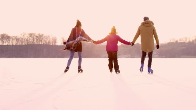 4k family holding hands ice skating on frozen lake, slow motion - zima filmów i materiałów b-roll