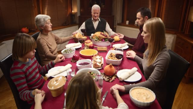 Family holding hands in prayer at Thanksgiving table video