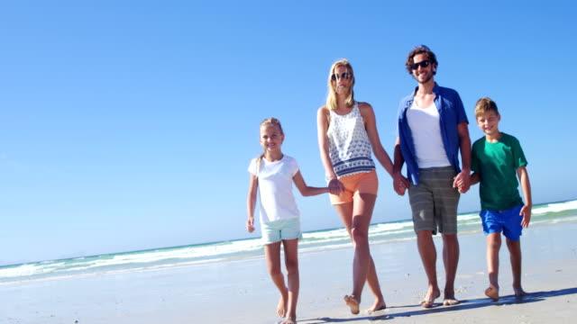 ビーチの海岸に歩きながら手を取り合って家族 ビデオ