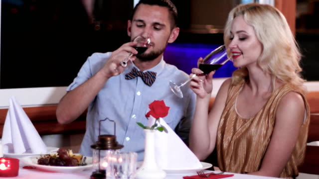 family holiday, husband and wife drinking wine from a glass, toast, romantic atmosphere, man and woman on a date in a restaurant, romantic supper in a restaurant video