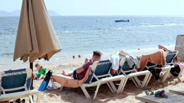 Family holidays on the beach of the Red Sea. A beach with deck chairs and beach umbrellas on the Red Sea in Egypt. Family with children resting on the beach.  Parents are lying on a deck chair and the children are playing nearby. sunbathing stock videos & royalty-free footage
