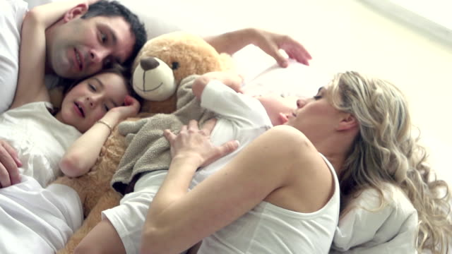 stockvideo's en b-roll-footage met slow motion - family hug bed fun sunday morning - bed