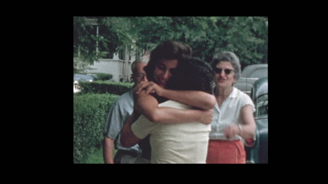 1957 Family hugs and kisses goodbye in front of vintage antique cars