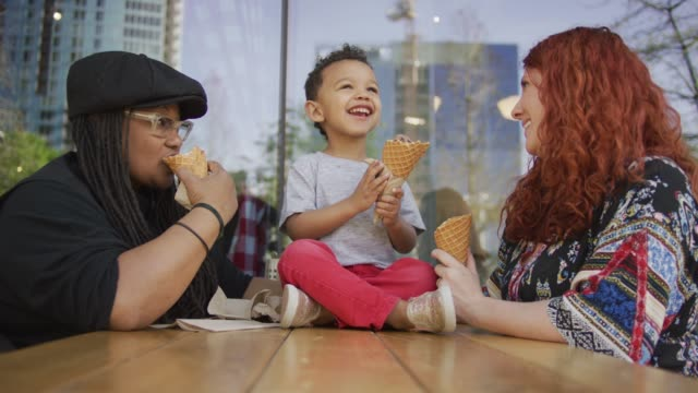 Family Ice Cream Outing A homosexual biracial female couple is having ice cream with their little boy. The boy is sitting cross-legged on the table. One woman is Caucasian and the other is African-American lesbian stock videos & royalty-free footage