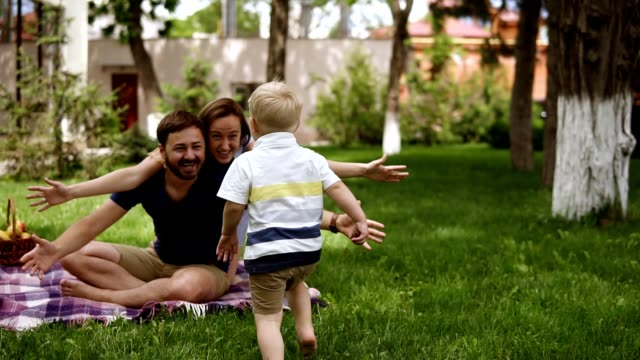 family idyll. happy child running to his parents in a blurred perspective. close up of young couple hugging his little blonde son while sitting on the grass, plaid. picnic in the park. slow motion - genitori video stock e b–roll