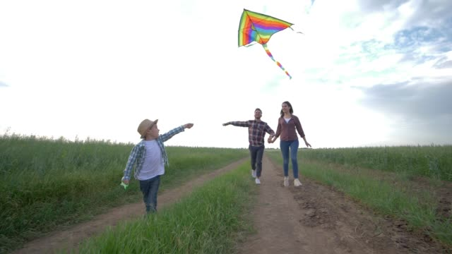 family idyll, little boy with kite in his hands runs on countryside in slow motion on background of young parents and sunny sky during weekend at nature