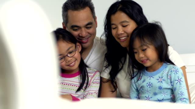 familie zusammen lesen im bett - philippinischer abstammung stock-videos und b-roll-filmmaterial