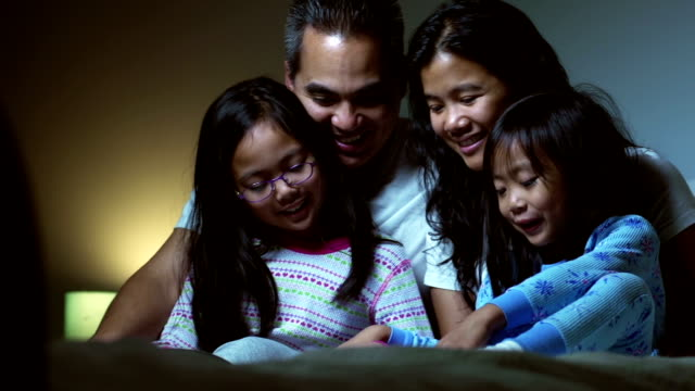 Family in bed together reading video