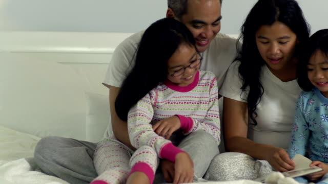 семья в постели вместе - филиппинского происхождения стоковые видео и кадры b-roll