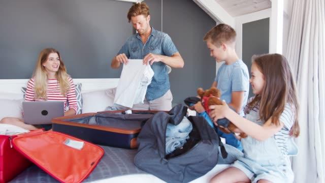 stockvideo's en b-roll-footage met familie in slaapkamer koffers voor vakantie en laptop gebruikt - ingepakt