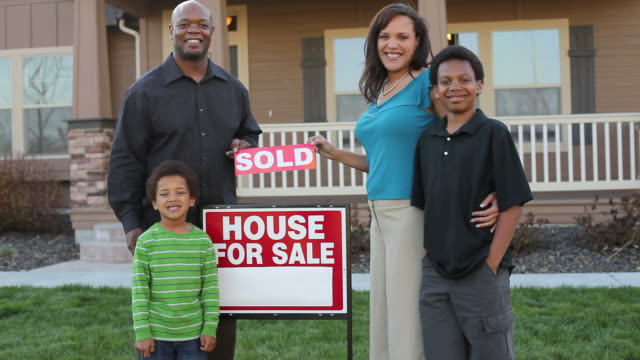Family in front of home with sold sign  mid adult stock videos & royalty-free footage