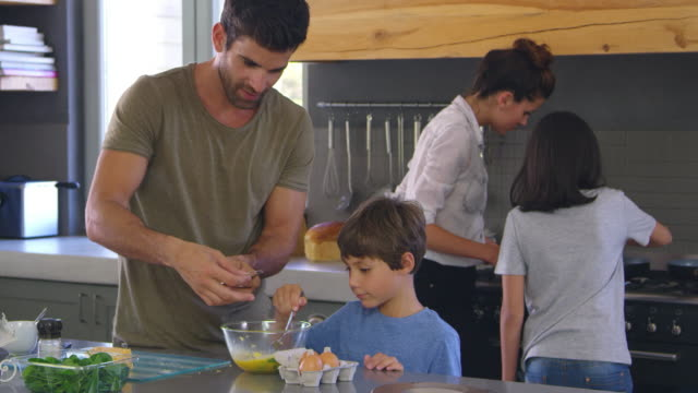 Family In Kitchen Making Morning Breakfast Together video