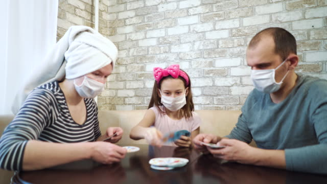 Family in medical masks having fun at home during pandemic Parents and little daughter wearing medical masks playing board game at home, mother wearing towel on head. Young family having fun at home quarantine during coronavirus pandemic wearing a towel stock videos & royalty-free footage
