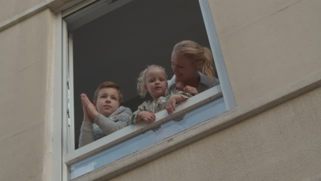family in open window during covid-19 quarantine - battere le mani esprimere a gesti video stock e b–roll