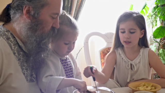family in traditional russian clothing eating dessert - славянская культура стоковые видео и кадры b-roll