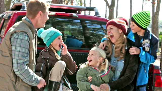 Family in warm clothing laughing on back of pickup video