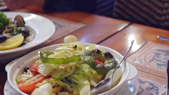 vídeos y material grabado en eventos de stock de la familia está comiendo, disfrutando de deliciosas verduras al horno variadas, almejas salteadas, bola de bacalao frito en el restaurante portugués de macao, estilo de vida. - pimiento verde