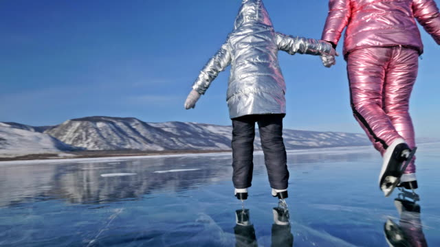 vídeos de stock e filmes b-roll de family is ice skating at day. girls to ride figure ice skates in nature. mother and daughter riding together on ice in cracks. outdoor winter fun for athlete nice winter weather. - lago baikal