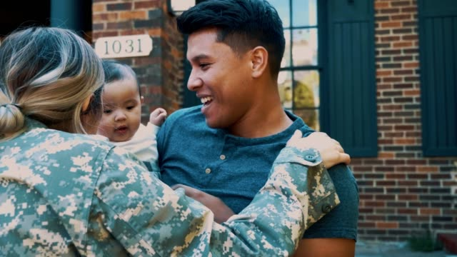 A family is reunited after a soldier returns home After returning home from military duty, a female soldier is greeted outdoors by her husband and baby daughter. They share kisses and embraces. camouflage clothing stock videos & royalty-free footage