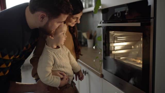 Family is waiting for meal to be done Young family with son is looking in the oven and waiting for their meal to be done. baked stock videos & royalty-free footage