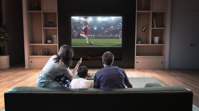 A family is watching a soccer moment on the TV and celebrating a goal A family is watching a soccer moment on the TV and celebrating a goal, sitting on the couch in the living room. The living room is made in 3D. match sport stock videos & royalty-free footage