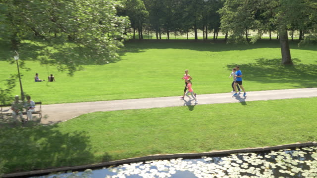 AERIAL Family jogging in the park along a lake