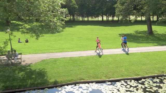 vídeos de stock e filmes b-roll de família aérea jogging no parque juntamente com um lago - parque público