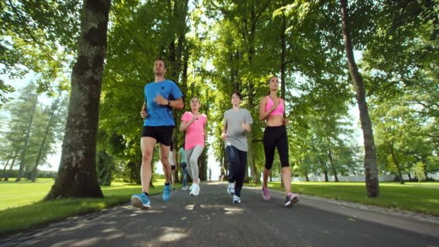 stockvideo's en b-roll-footage met slo mo ts familie joggen door avenue in een prachtig park - vier personen
