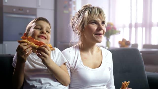 vídeos de stock e filmes b-roll de family laughing, eating pizza and watching cartoon - tv e familia e ecrã