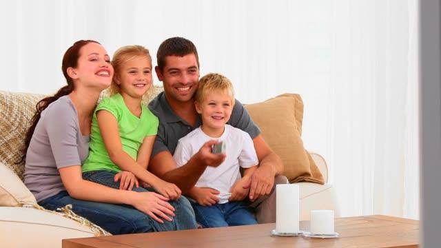 vídeos de stock e filmes b-roll de família rir na frente da tv - tv e familia e ecrã