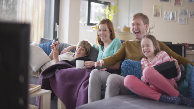 Family laughing watching TV on the sofa Wide handheld shot of a family of four watching TV on the sofa and laughing. Shot in Slovenia. family watching tv stock videos & royalty-free footage