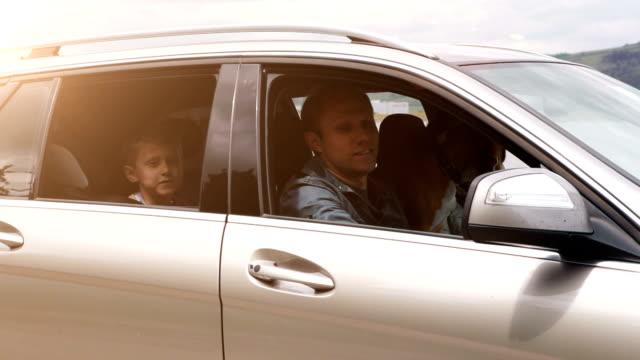 Familia va en un coche: ondas muchacho feliz de la ventana abierta - vídeo