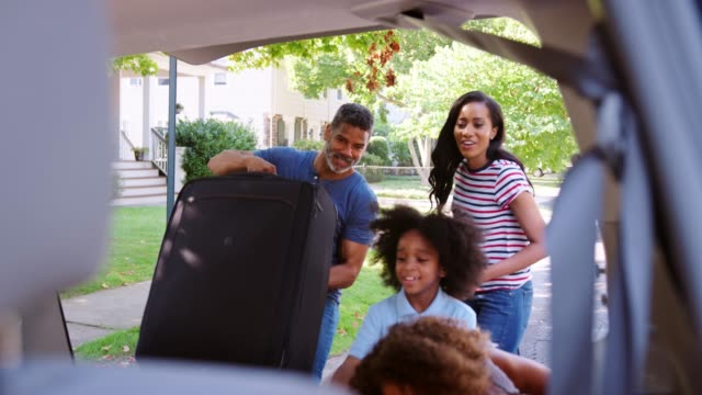family leaving for vacation loading luggage into car - viaggio in macchina video stock e b–roll