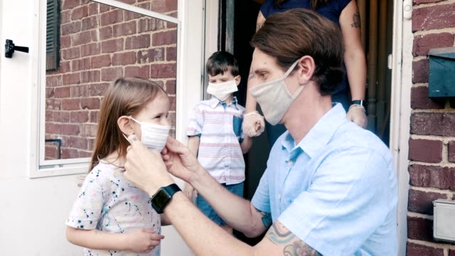 Family leaving home during the COVID-19 pandemic A mid adult father places a protective face mask on his young daughter as they prepare to leave their home during the COVID-19 pandemic. He then leads his daughter from their home as his wife and young son follow behind them. human relationship stock videos & royalty-free footage