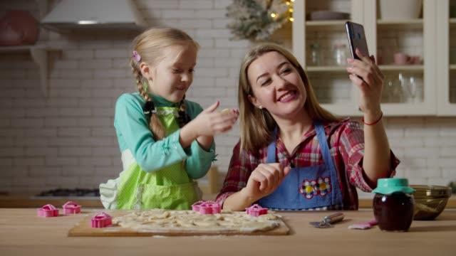 familj live streaming med telefon under matlagning - videor med baka bildbanksvideor och videomaterial från bakom kulisserna