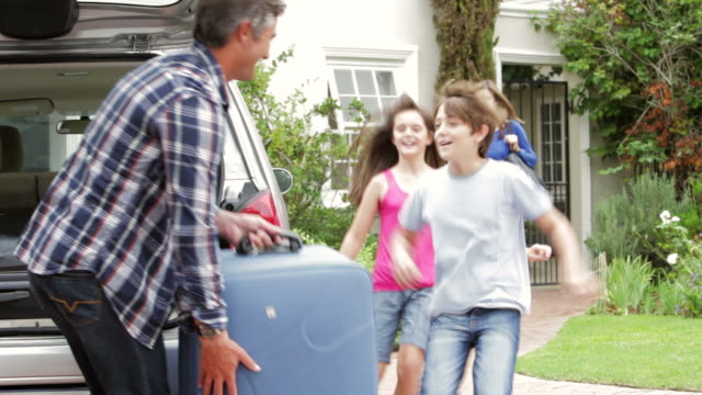 stockvideo's en b-roll-footage met family loading luggage into boot of car ready for holiday - packing