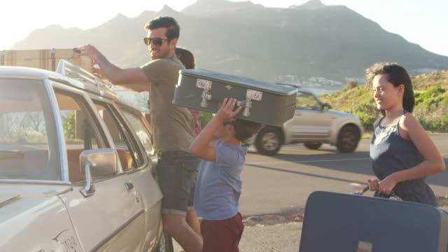 Familia cargando equipaje en coche techo listo para el viaje - vídeo