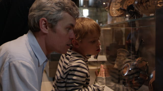 family look at artifacts in case on museum trip shot on r3d - museo video stock e b–roll