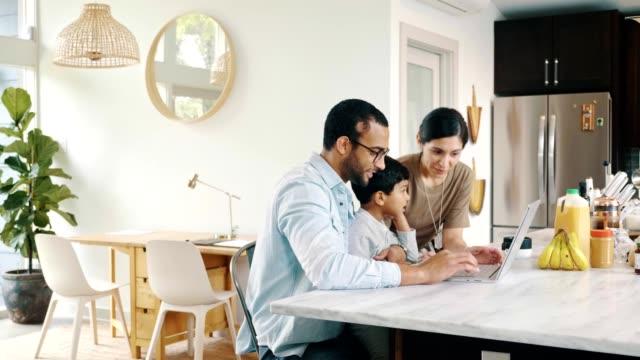 familie schaut gemeinsam auf den computer, während sie zu hause ist - person gemischter abstammung stock-videos und b-roll-filmmaterial