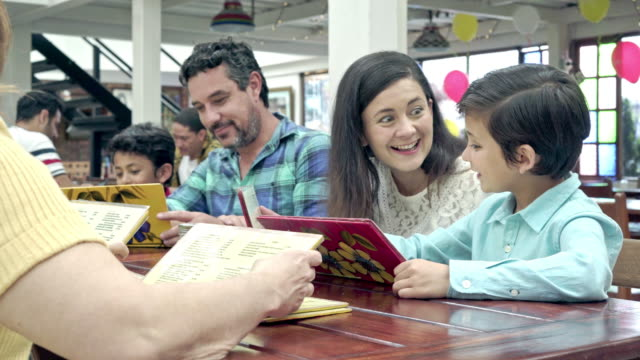 Family looking at the menu to choose who wish to have lunch
