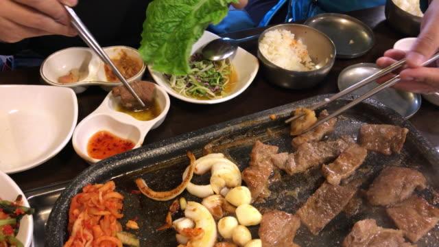 family lunch time with korean bbq , seoul , south korea - cultura coreana video stock e b–roll