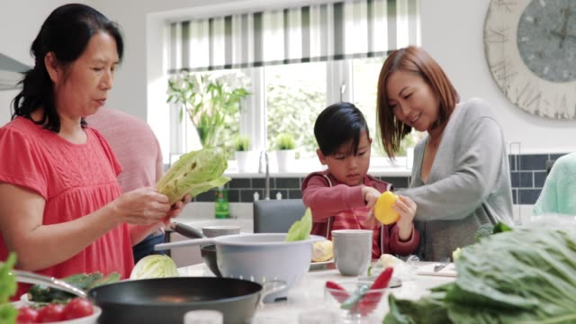 Family Making a Stir Fry Together Three generation family are all helping to make a stir fry together at home. stir fried stock videos & royalty-free footage