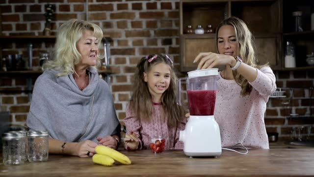 Family making berry smoothie in the kitchen video