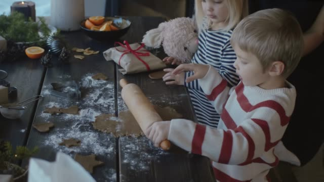 vídeos de stock e filmes b-roll de family making gingerbread cookies for christmas  (slow motion) - christmas cookies
