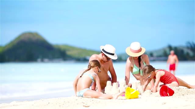 夏の休日の白いビーチに家族の作る砂の城 - ファミリーバケーション点の映像素材/bロール