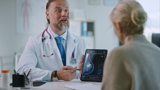 stockvideo's en b-roll-footage met huisarts toont mammografie testresultaten aan een senior patiënt op een tablet computer in een kliniek. vriendelijke assistent legt belang van borstkanker preventie screening. - breast cancer