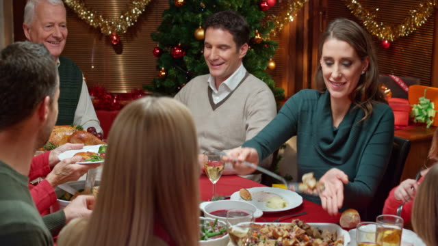 stockvideo's en b-roll-footage met family members sharing food at the christmas table - kerst