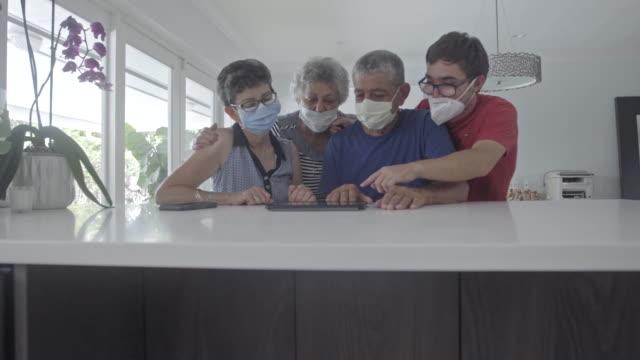 stockvideo's en b-roll-footage met familieleden die maskers binnen dragen - latijns amerikaanse en hispanic etniciteiten