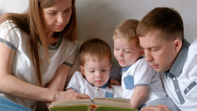 family mom, dad and two twin brothers read books laying on the bed. family reading time. - attività del fine settimana video stock e b–roll